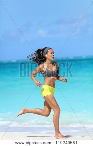 Active, healthy and fit lifestyle - woman running barefoot on beach. Asian female runner jogging full length on sand training her leg muscles and cardio on ocean background.