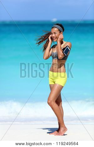 Running woman wearing earphones and phone arm strap with touchscreen listening to music for workout motivation. Female athlete standing full body on beach putting on in-ear headphones for exercise.