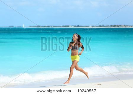 Female runner running on beach - summer vacations exercise. Asian female athlete strength training during holiday travel working out her cardio listening to music on her smartphone with sport armband.