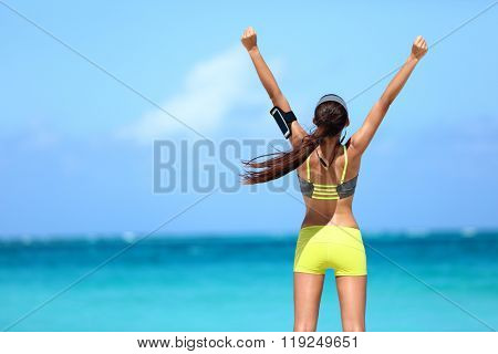 Success fitness woman concept with sports armband and earphones. Winning concept of female athlete runner cheering with arms raised up for achievement in weight loss or life goal.