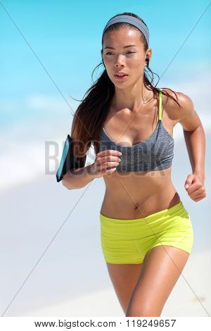 Young fit Asian woman runner running on beach training her cardio exercising getting in shape for summer vacations. Weight loss - active healthy living concept.