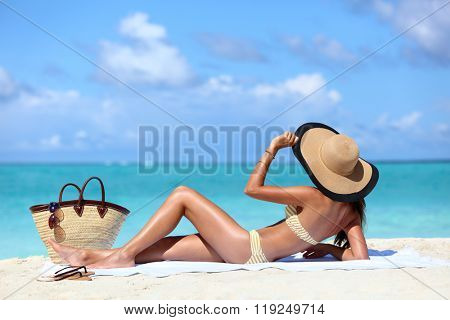 Sexy bikini woman tanning relaxing on beach. Suntan concept. Unrecognizable female adult from the back lying down with straw hat sunbathing under the tropical sun on Caribbean vacation.