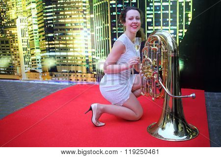 Beautiful woman with glass of champagne near the brass tube on the red carpet