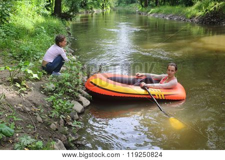 Woman with oars in a rubber boat on the shore near the girl