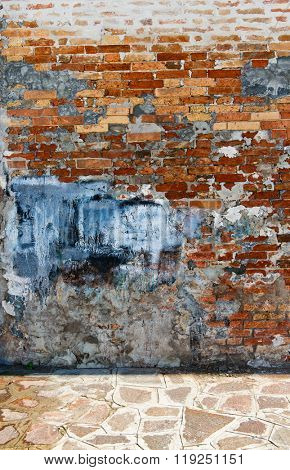 Abstract Background of Chipped and Weathered Brick Wall in Urban Setting - Eroding Brick Wall with Stone Sidewalk
