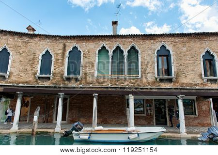 Gothic windows in the front facade of a building overlooking a canal and moored boat on Murano, Venice , Italy, known for its glass manufacture