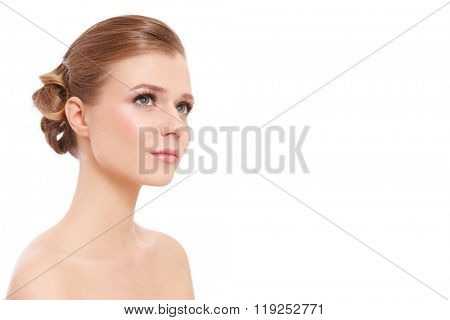 Young beautiful woman with prom hairdo and clean make-up looking upwards over white background, copy space