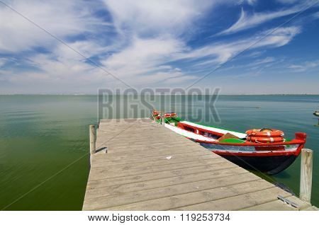 Pier and wooden boat in Albufera lake, Valencia, Spain.