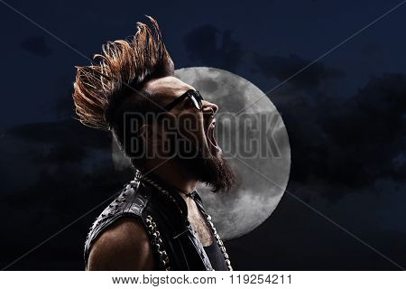 Young man with a Mohawk hairstyle shouting in the night in front of a full moon