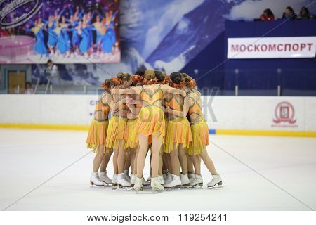 MOSCOW - APR 26, 2015: The girls in a beautiful yellow dress formed a small circle on the ice at the Cup in synchronized figure skating in the sports complex Olympiysky