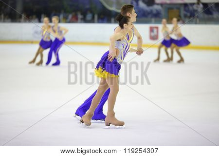 MOSCOW - APR 26, 2015: A pair of figure skaters in blue and yellow suits on ice at the Cup in synchronized figure skating in the sports complex Olympiysky