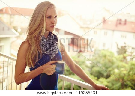 Portrait of daydreaming young woman drinking tea, smiling on balcony.