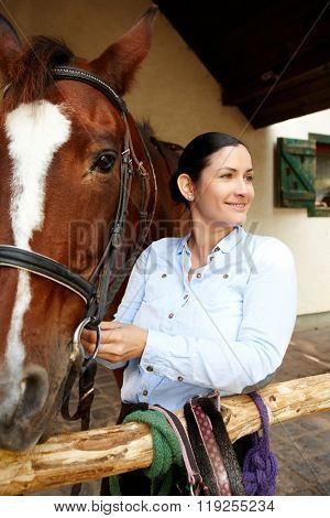 Happy young woman standing by horse, smiling, looking away.