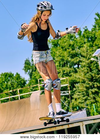 Teen girl in helmet rides his skateboard outdoor. Girl do  stunt aganist blue sky. Outdoors.