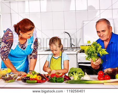 Grandfather and grandmother learn child cooking.