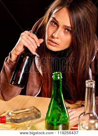 Drunk girl holding bottle of alcohol. Soccial issue alcoholism on black background.