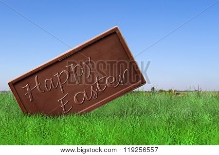 Happy Easter text on chocolate bar on field background