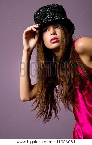 Gorgeous young fashion girl with pink dress and hat fashion shot