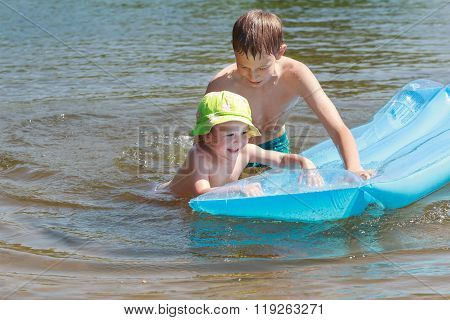 Sibling children having fun with inflatable blue pool lilo in summer lake outdoor