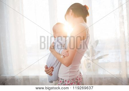 Little Baby In The Arms Of Her Mother Living Room.