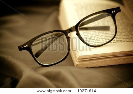 Selective Focus Of Reading Eyeglasses Wiht Opened Book