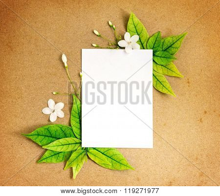 The White Blank Paper Sheet With Fresh Spring  Green Leafs Border Frame On Brown Recycle Paper Backg