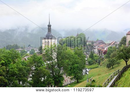 GRUYERES, SWITZERLAND - JULY 8, 2014: St. Theodul's Church, and the town of Gruyeres. Seen from Gruyeres Castle the surrounding hills are shrouded in clouds.