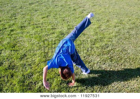 Boy doing somersaults on green grass