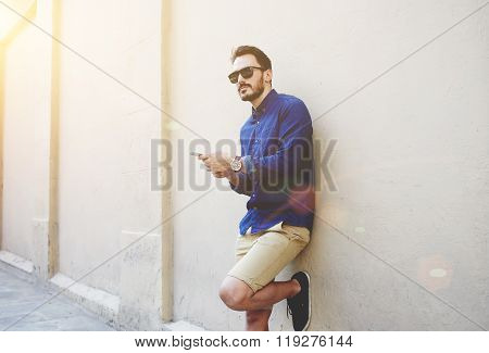 Confident bearded man holding in and mobile phone while standing near street wall in sunny summer