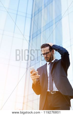 Man investor reading shocking news on mobile phone about falling shares on stock exchanges
