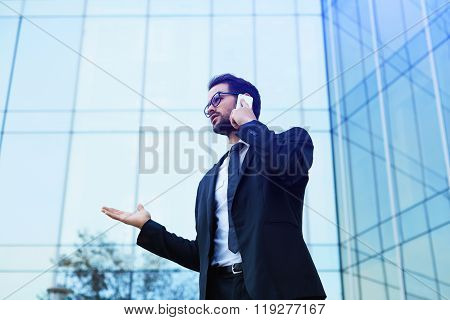 Young official man expert calling via cell telephone while standing outdoors near modern building