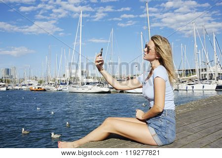 Female wandered making photo with mobile phone camera while sitting on the wooden pier near sea port