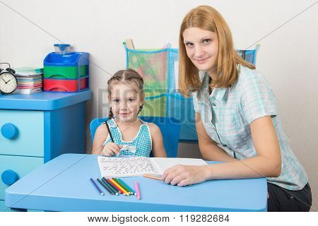 Young Girl Sitting At A Table With A Five-year Girl And Deals With Spelling