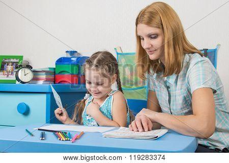 Girl Enjoys Painting With Teacher In Kindergarten
