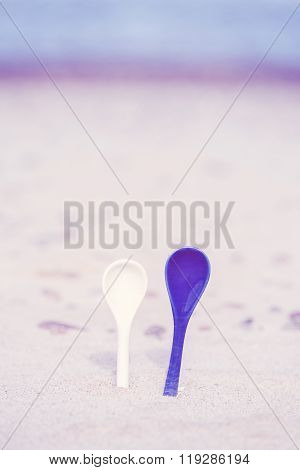 Vintage Stylized Two Porcelain Spoons Stuck In Sand, Shallow Depth Of Field