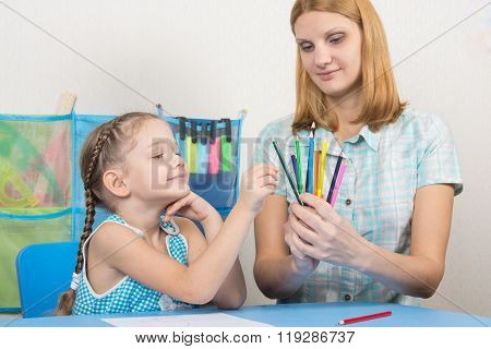 The Five-year Child Picks A Pencil In The Hands Of Mother