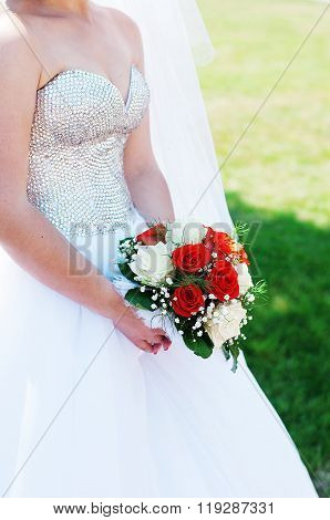 Close view of beautiful colorful wedding bouquet in a hand of a