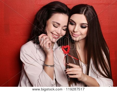 two beautiful smiling girls with dark hair posing together