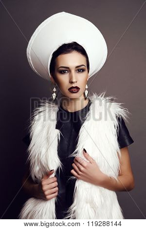 gorgeous woman with dark hair and bright makeup, wears extravagant outfit