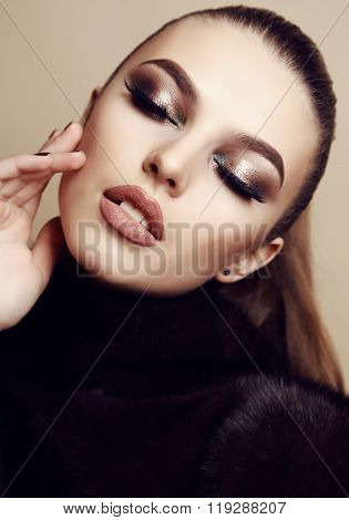 beautiful young woman with dark hair and evening makeup, wears fur coat