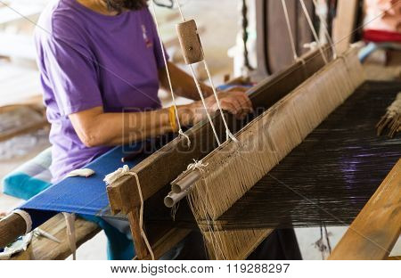 LAMPHUN, THAILAND - FEBRUARY 17: Woman using traditional loom to weave thailand textile at Tonkaew temple in Lamphun, Thailand on February 17, 2016.