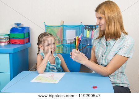 Five-year Girl Choose The Right Pencil From The Teacher Hands