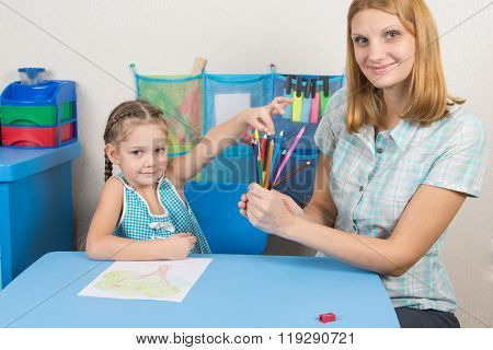 Five-year Girl Choose The Right Pen From The Hands Of The Educator, All Looked In The Frame