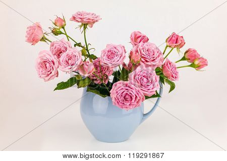 Pink flowers in blue jug. Roses in jug. Flowers in vase. Vintage background. Shabby chic concept.