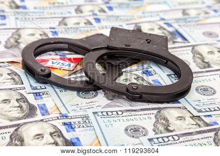 Steel Handcuffs And Credit Cards Lying On The Background Of American Dollars