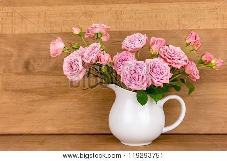Pink flowers in white jug. Roses in jug. Wooden background. Flowers in vase. Shabby chic concept.