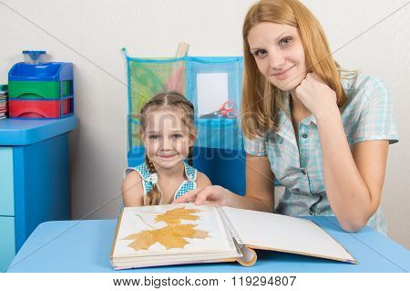 Five-year Girl And Mother Looking At The Herbarium Of The Leaves In The Album And Looked In The Fram