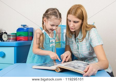 Five-year Girl And Mother Looking At The Photos In The Album At The Table At Home