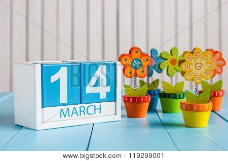 March 14th. Image of march 14 wooden color calendar with flower on white background.  Spring day