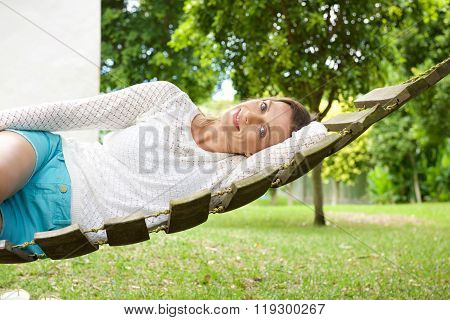 Attractive Older Woman Lying On Hammock In Garden
